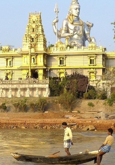Fishermen taking out under the watchful eye of Shiva in Murudeshwara, Karnataka, India